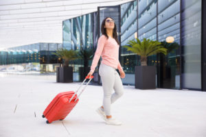 positive young Indian woman student in sunglasses leaving airport hall
