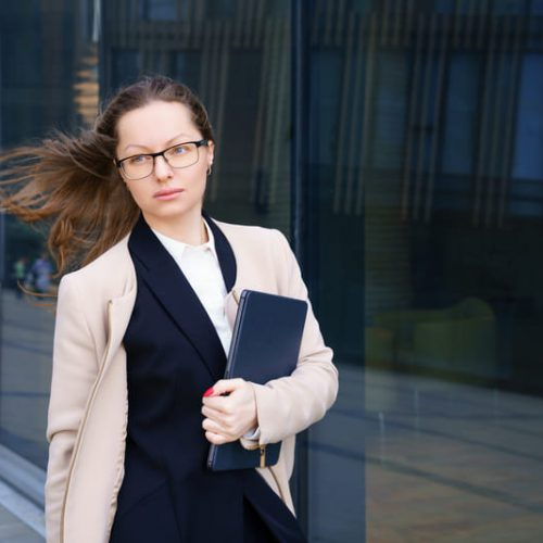 business-woman-stands-with-laptop-suit-glasses-outside-office-building-during-day